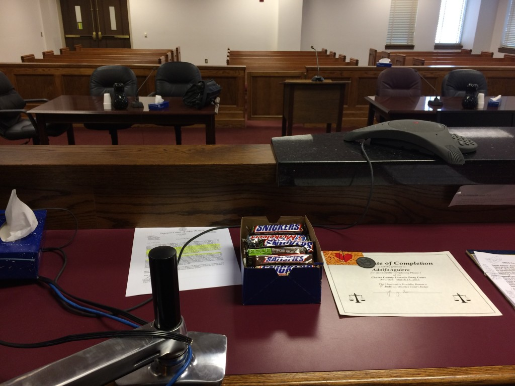 Judge Freddie Romero gives candy bars to the kids who have a good day in Drug Court. Credit Marisa Demarco / KUNM
