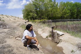 Grow the Future director Travis McKenzie sits by the acequia that waters the community farm Credit Ed Williams-KUNM
