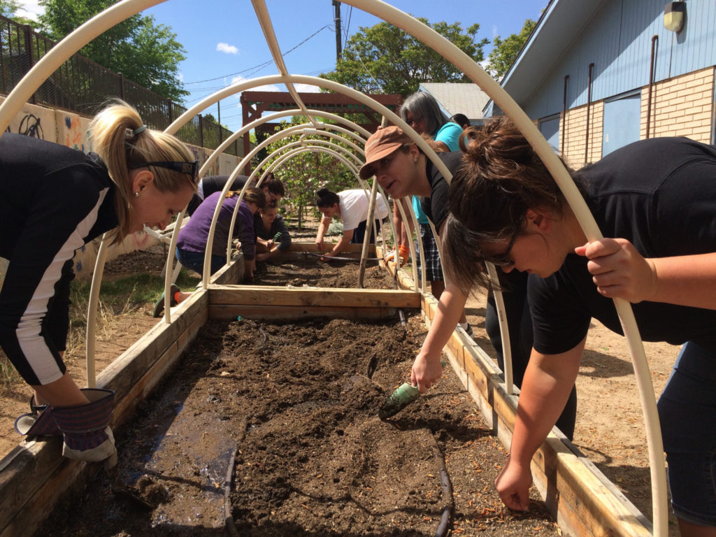 Women at Maya's Place and volunteers work on the shared garden. —Photo by Marisa Demarco / KUNM