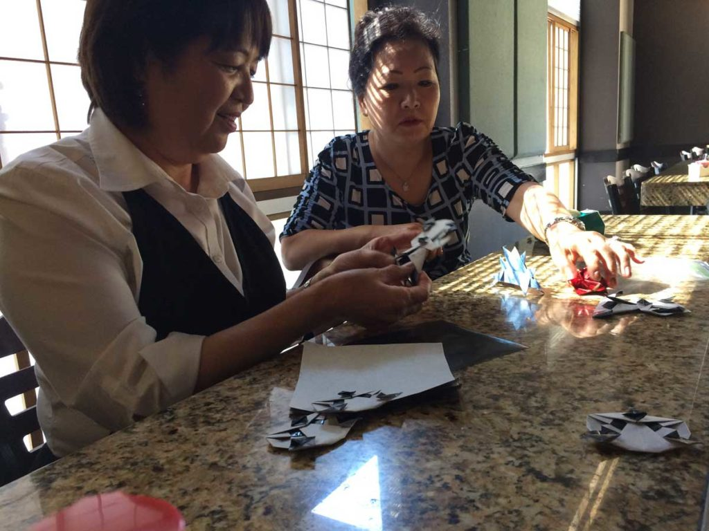 Bar Manager Setsuko Rosado and Head Hostess Kum Chu Tillery fold origami on their break. Credit Marisa Demarco / KUNM