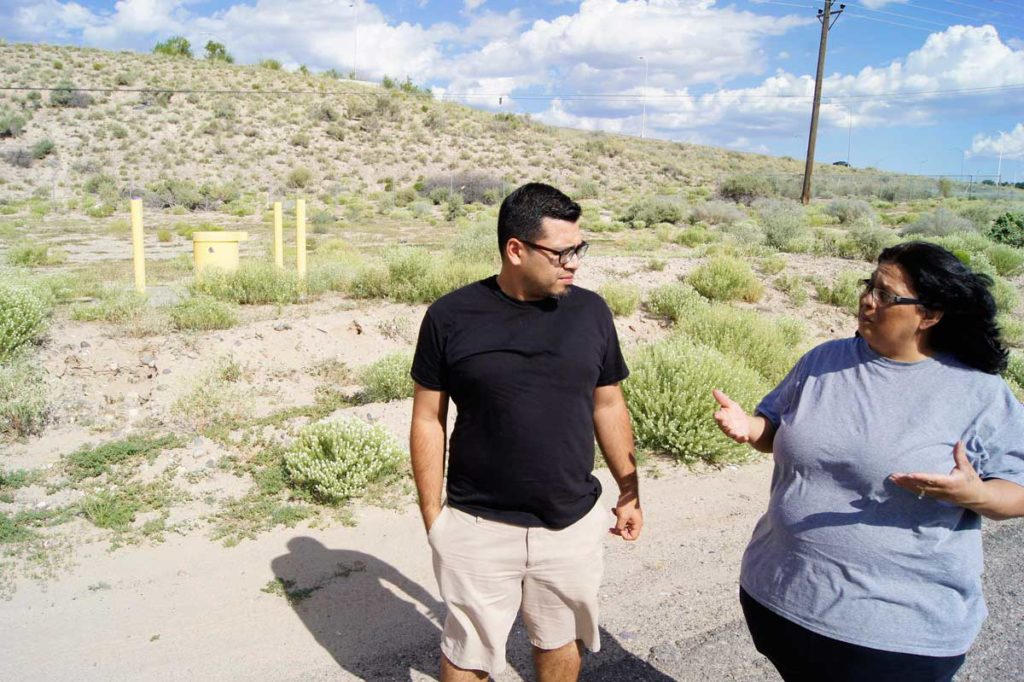 Juan Reynosa of the Southwest Organizing Project and Esther Abeyta of the San Jose Neighborhood Association stand at the site of the proposed road project. To the left is a well that is part of the South Valley Superfund site. ED WILLIAMS
