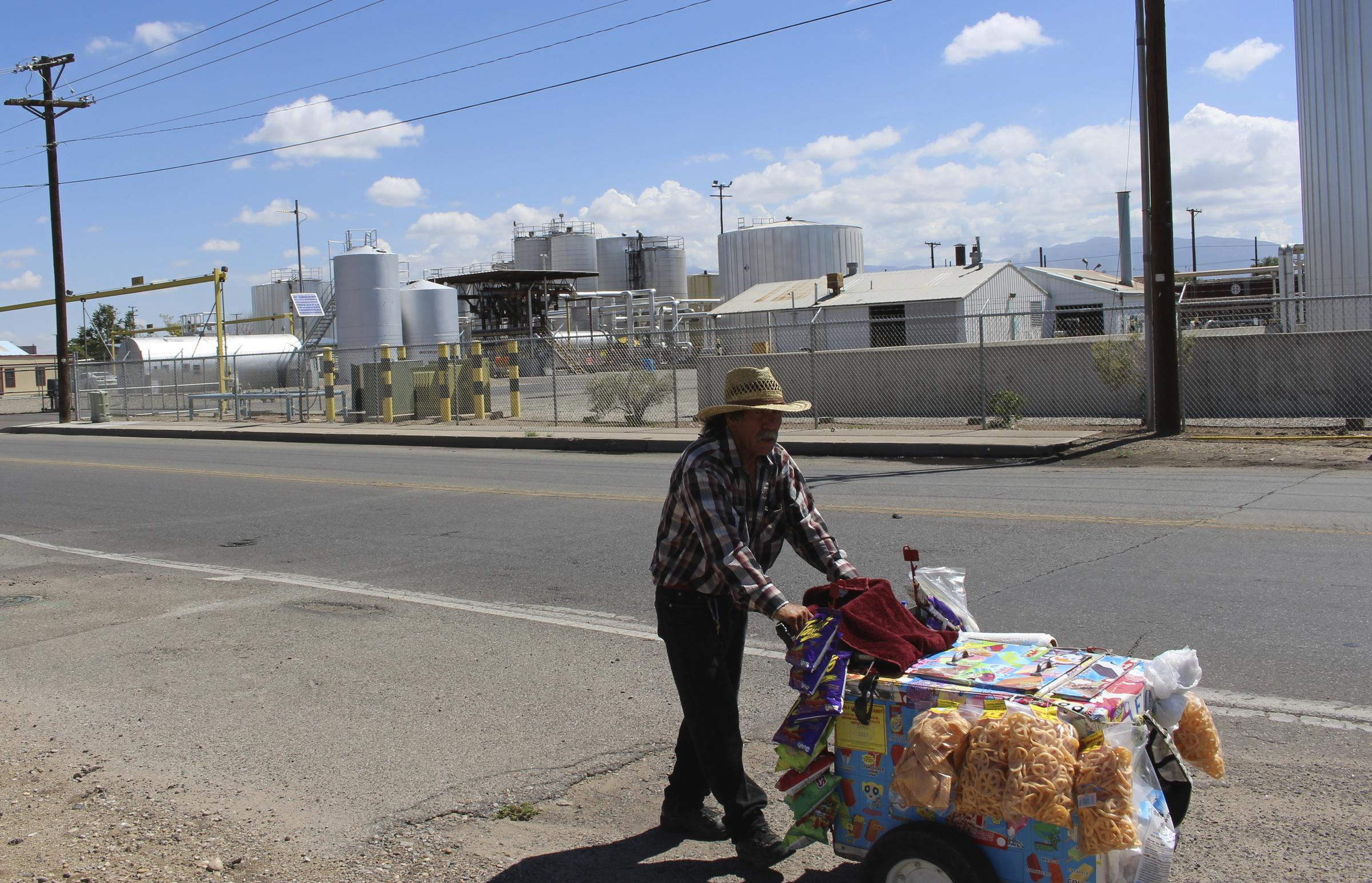 A vendor pushes his cart past the Western Refining asphalt plant on Second St SW in Albuquerque. Ed Williams
