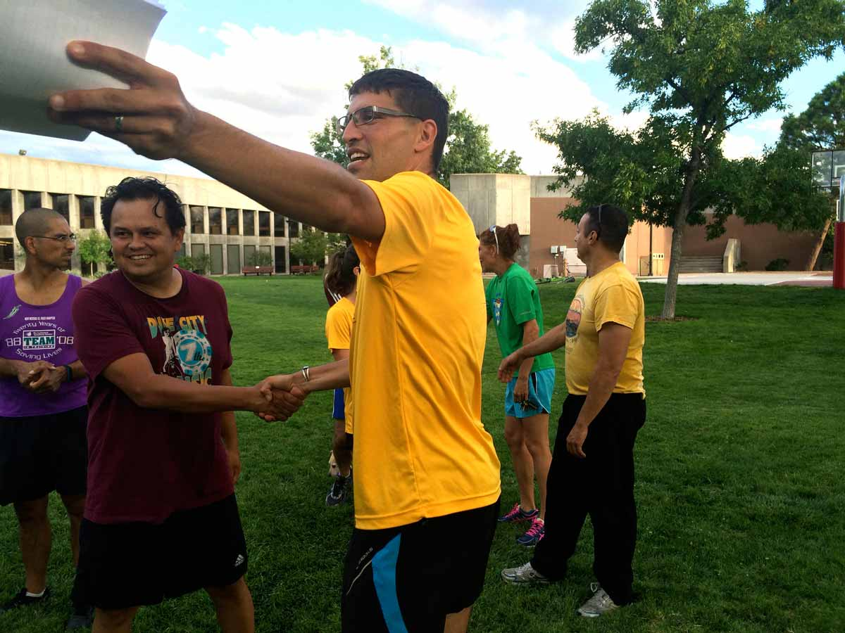 Dr. Anthony Fleg shakes hands with a runner. Credit Marisa Demarco / KUNM