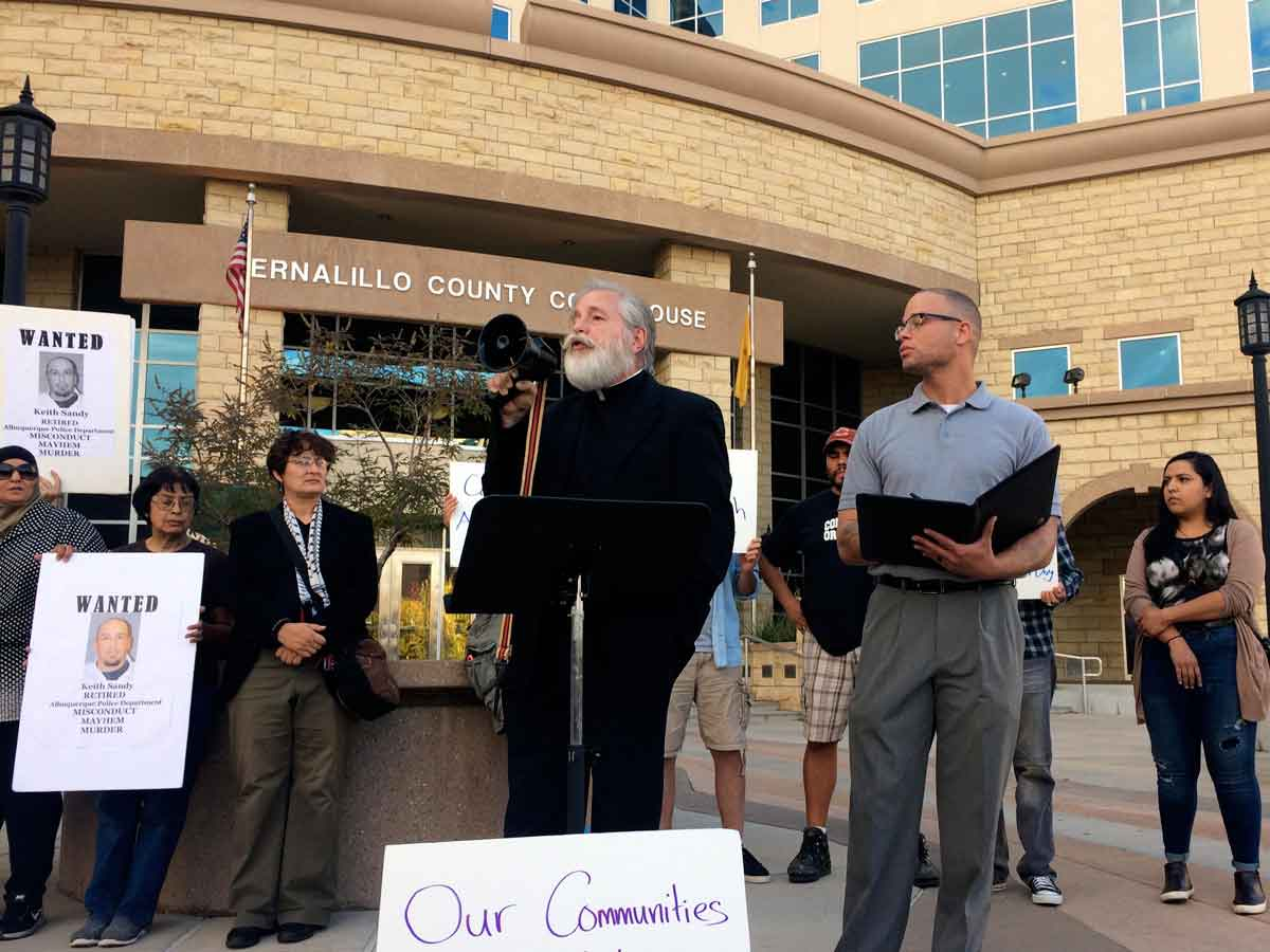 Father Frank Quintana speaks to a small crowd gathered in front of the Bernalillo County Courthouse. Marisa Demarco / KUNM