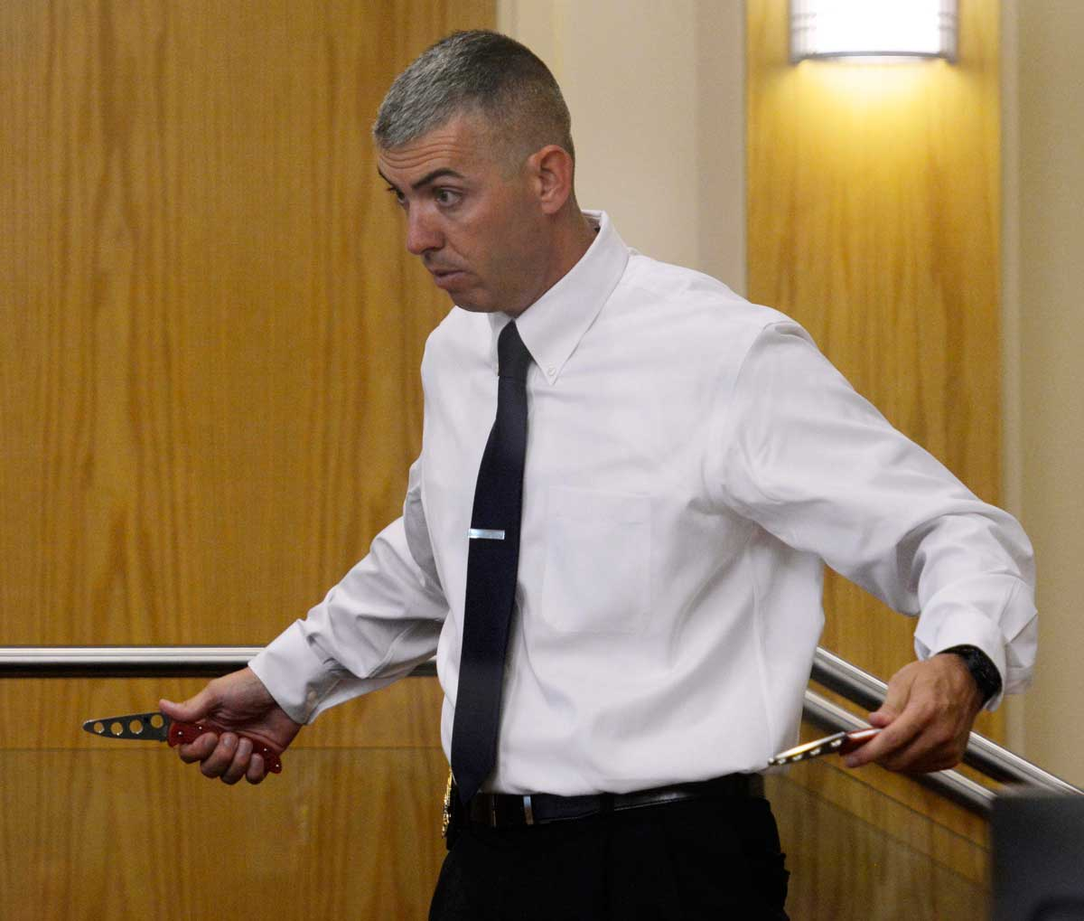 Albuquerque Police Sgt. Richard Ingram shows the jury how James Boyd would pull out two knives from his pockets. Greg Sorber / Albuquerque Journal